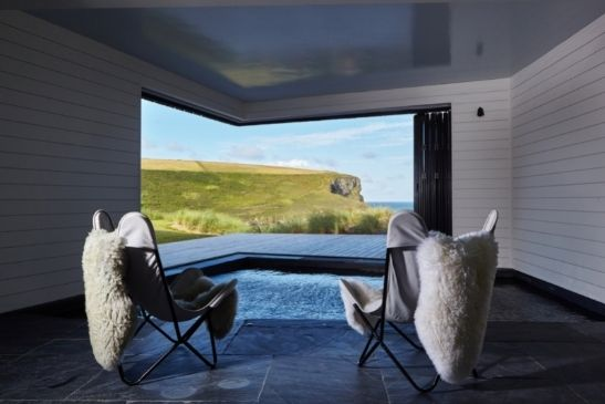 bifolds in a corner opening configuration by an indoor dipping pool in a luxury coastal home