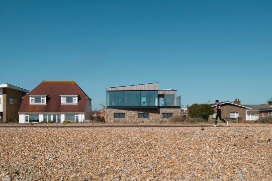 contemporary seafront home with floor to ceiling glazing and stoner external building finishes
