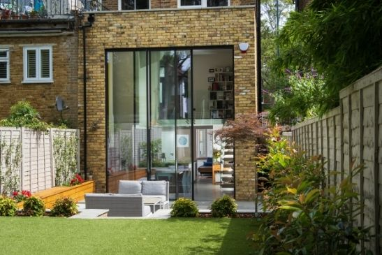 external view of a double height extension as part of a London home renovation with tall sliding glass doors