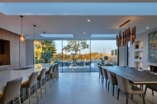 sliding pane with three panes by a large open plan luxury kitchen diner area