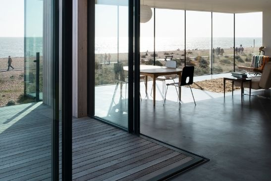 corner opening slim sliding glass doors creating an indoor-outdoor living space in a luxury home by the sea