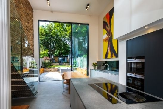 modern double height kitchen and diner area with luxury interior design and oversized sliding glass doors to create a striking glazing elevation