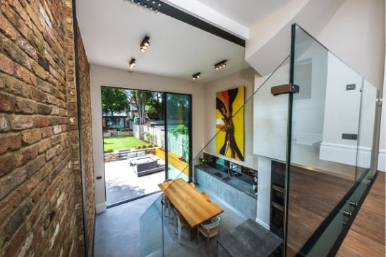 mezzanine floor level in a double height extension in London with 4.5m tall minimal windows sliding glass doors