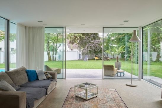 sliding glass door with floor to ceiling glass and fixed panes to create impressive glass walls