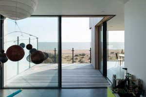 corner opening sliding glass doors leading to a seafront decking in a luxury coastal home