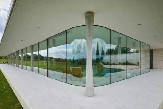 curved glass and minimal windows triple glazed 4+ sliding glass doors by an indoor pool in a luxury new build home