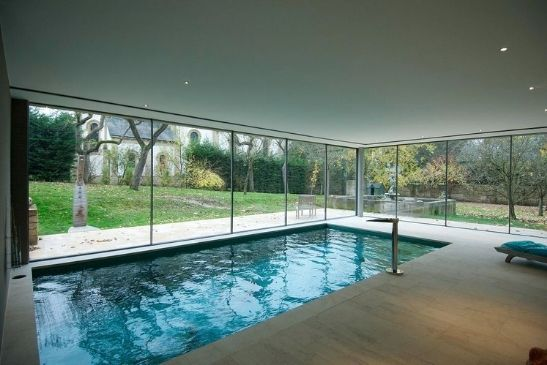 indoor pool area surrounded by sliding glass walls made from minimal windows sliding glass doors