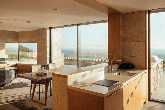 luxury coastal holiday homes nestled into a cliff side with slim sliding doors providing stunning sea views