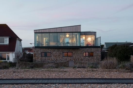 new build home on a west Sussex beach with floor to ceiling minimal windows sliding glass doors and a natural stone exterior