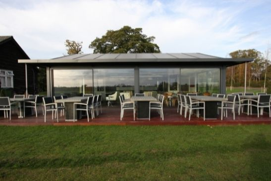 pitch side polo pavilion with minimal windows sliding glass doors and an outdoor decking seating area