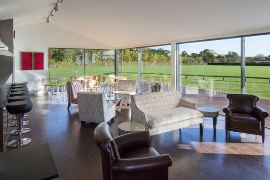 unique and quirky interior design of a polo pavilion with three sets of two pane minimal windows sliding doors