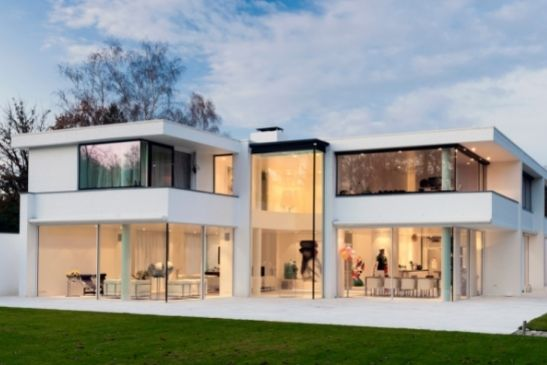 double height glass façade and minimal windows slim sliding doors used in a luxury new build home