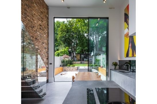 three pane double height sliding glass door with minimal aluminium framing in a double height kitchen-diner